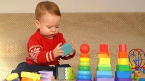 Kind, das bunte Spielwaren spielt stock video