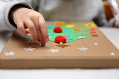 Kind, das Dekoration für Weihnachten macht Lizenzfreie Stockbilder