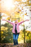 Kind, das in den Fall-Blättern spielt lizenzfreie stockbilder