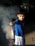 Kind, das den Kracher beleuchtet Stockbilder