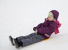 Kind, das in den Schnee schiebt Stockbild