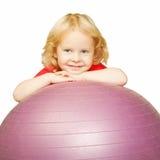 Kind, das den Sport, lächelnd auf fitball spielt Stockfotos