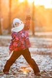Kind, das in den Strahlen der untergehenden Sonne mit der angehobenen Hand, Winter steht Lizenzfreies Stockfoto