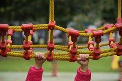 Kind, das den verrückten Spaß spielt mit kletterndem Netz - Spielplatz hat Stockbild