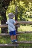 Kind, das den Zaun klettert Lizenzfreies Stockfoto