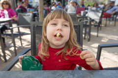 Kind, das in der Außenstange isst Käsehauch sitzt Lizenzfreies Stockbild