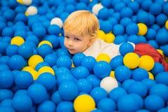 Kind, das in der Ballgrube spielt Bunte Spielwaren f?r Kinder Kindergarten oder Vorschule- Spielraum Kleinkindkind an der Tagesbe lizenzfreie stockfotografie