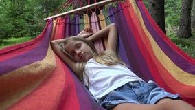 Kind, das in der Hängematte beim Kampieren, Kind sich entspannt im Wald, Mädchen in den Bergen schläft stock footage