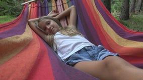 Kind, das in der Hängematte beim Kampieren, Kind sich entspannt im Wald, Mädchen in den Bergen schläft stockbild