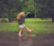 Kind, das in der schmutzigen Schlamm-Pfütze spritzt Lizenzfreie Stockfotografie