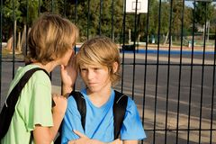 Kind, das an der Schule flüstert stockfotografie