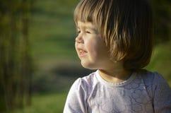 Kind, das an der Sonne blinkt Lizenzfreies Stockfoto