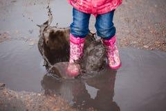 Kind, das die rosa Regenstiefel springen in eine Pfütze trägt Stockbilder