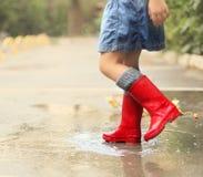 Kind, das die roten Regenstiefel springen in eine Pfütze trägt Lizenzfreie Stockbilder