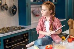 Kind, das digitale Tablette hält und weg beim Sitzen schaut lizenzfreie stockbilder