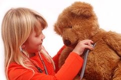 Kind, das Doktor mit ihrem Bären spielt stockfotos