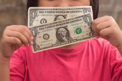 Kind, das Dollargeld hält stockfotografie