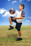 Kind, das draußen Fußball spielt Lizenzfreie Stockbilder