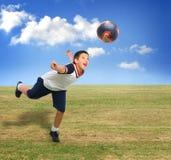 Kind, das draußen Fußball spielt Stockbild