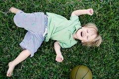 Kind, das draußen im Gras lacht Stockfotos