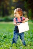 Kind, das draußen mit Tablette spielt Stockbilder