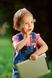Kind, das draußen mit Tablette spielt Stockfotografie