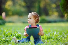 Kind, das draußen mit Tablette spielt Stockfotos