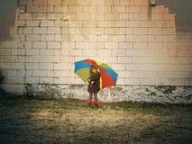 Kind, das draußen Regenbogen-Regenschirm hält lizenzfreie stockfotografie
