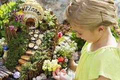 Kind, das draußen feenhaften Garten in einem Blumentopf betrachtet Lizenzfreie Stockfotos