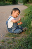 Kind, das durch den Straßenrand sitzt Lizenzfreies Stockbild