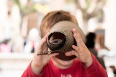 Kind, das durch ein Blatt Papier schaut lizenzfreie stockfotos