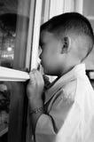 Kind, das durch ein Fenster, Kindsehnsucht schaut Lizenzfreies Stockfoto