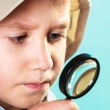 Kind, das durch eine Lupe schaut stockfotos