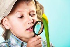 Kind, das durch eine Lupe schaut stockbild