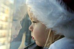Kind, das durch Fenster am sehr kalten Tag schaut Stockfoto