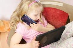 Kind, das durch Mobile spricht und in der Tablette spielt Stockfotos