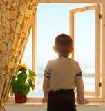 Kind, das durch offenes Fenster schaut Lizenzfreies Stockfoto