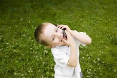 Kind, das durch Phone spricht lizenzfreie stockfotografie