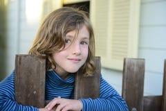 Kind, das durch Stangen des Zauns schaut Lizenzfreie Stockfotografie