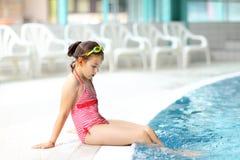 Kind, das durch Swimmingpool sich entspannt Stockfoto