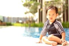 Kind, das durch Swimmingpool sitzt Stockbild