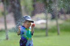 Kind, das durch Wasser gesprüht wird Lizenzfreie Stockfotos