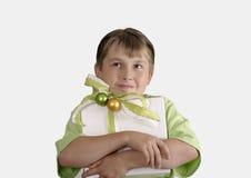 Kind, das ein eingewickeltes Geschenk anhält und durchdacht oben schaut stockfotografie