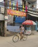 Kind, das ein Fahrrad mit der 2019 guten Rutsch ins Neue Jahr-Fahne im Hintergrund, Phuong Nam, Vietnam reitet stockbild