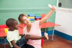 Kind, das ein Foto mit seinem Lehrer macht Lizenzfreies Stockfoto