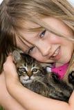 Kind, das ein Kätzchen streichelt. Stockbilder