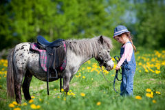 Kind, das ein kleines Pferd reitet Lizenzfreie Stockfotografie