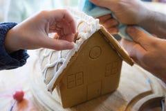 Kind, das ein Lebkuchenhaus mit Zuckerglasur und Bonbons baut Lizenzfreies Stockfoto