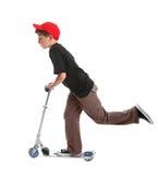 Kind, das ein Rollerspielzeug reitet Stockbild