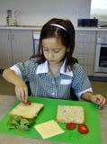 Kind, das ein Sandwich macht. Stockfoto